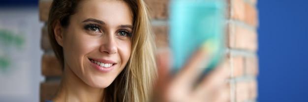 Primo piano di bella donna europea che sorride e che fa foto sul telefono. la donna non sposata scatta una foto del profilo sui social network
