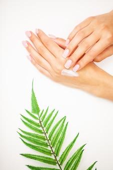 Primo piano di bella mano femminile che applica crema per le mani.