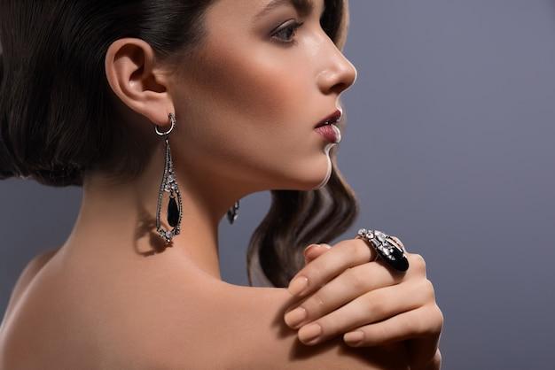 Primo piano di un bellissimo modello femminile in posa con grazia indossando un paio di orecchini e un anello con gemma nera su grigio