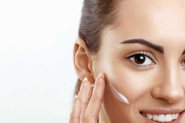 Primo piano di bella ragazza con prodotto di bellezza sul viso toccante trucco naturale della pelle morbida
