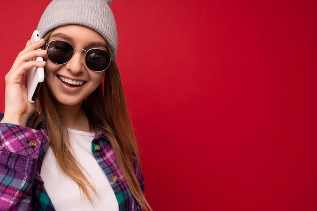 Primo piano bella felice giovane donna bionda positiva che indossa pantaloni a vita bassa camicia viola e casual
