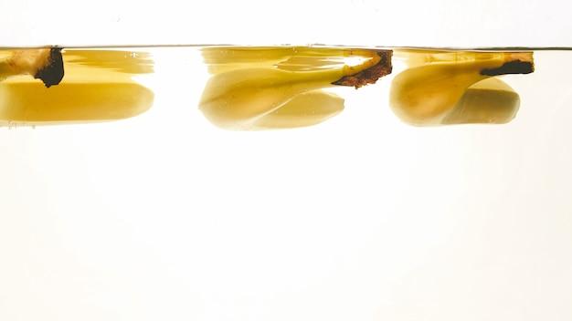 Primo piano bella immagine di banane che cadono in acqua chiara su sfondo bianco, un sacco di bolle d'aria fluttuanti e spruzzi d'acqua