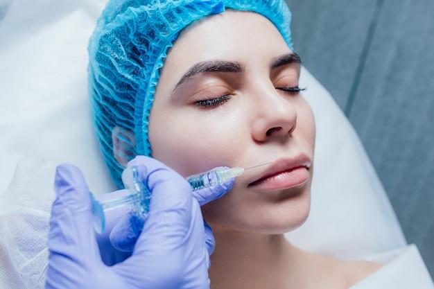 Primo piano di bella bocca e labbra con botox e siringa