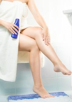 Bella donna del primo piano che applica crema idratante dopo la rasatura delle gambe