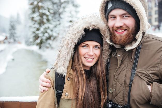 Primo piano di belle giovani coppie che stanno insieme sulla località di soggiorno di montagna di inverno