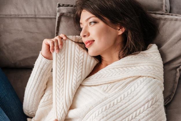 Primo piano di bella giovane donna sdraiata e rilassante sul divano