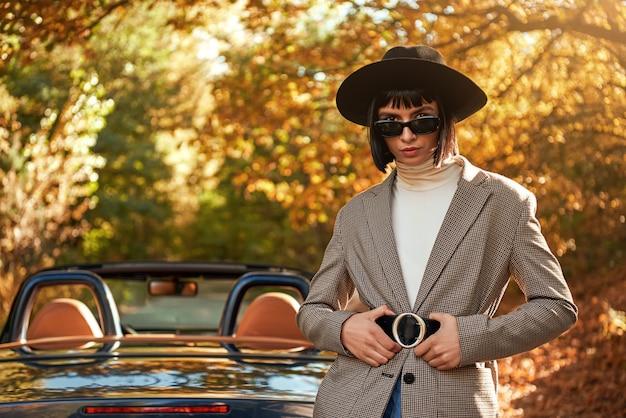 Primo piano di bella giovane donna che posa vicino alla stagione autunnale del cabriolet