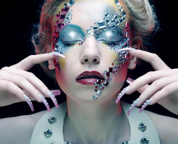 Ritratto di bellezza del primo piano del viso attraente modello con strass luminosi visage. donna con l'occhio chiuso.