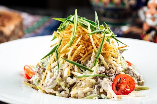 Primo piano su insalata di strisce di manzo con verdure e patatine sul tavolo di legno nero