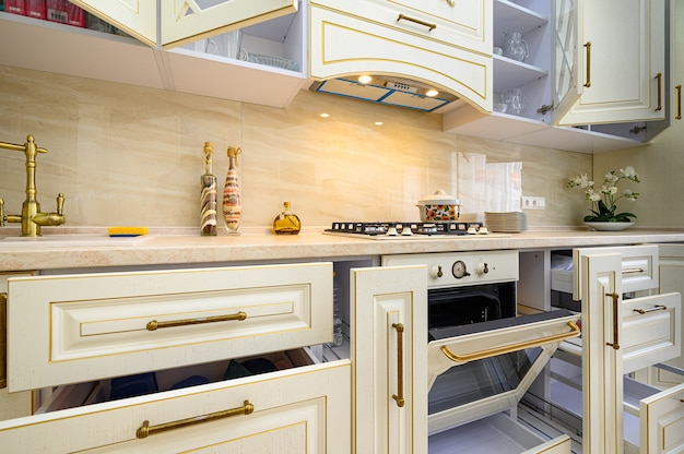 Primo piano alla cucina classica contemporanea beige interna progettata in stile provenzale, tutti i mobili con ante e cassetti aperti