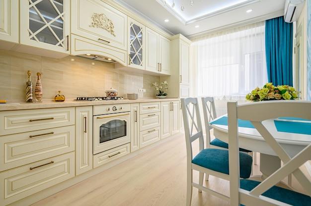 Primo piano su beige, bianco e ciano interno cucina classica contemporanea progettata in stile provenzale, tutti i mobili con ante e cassetti aperti