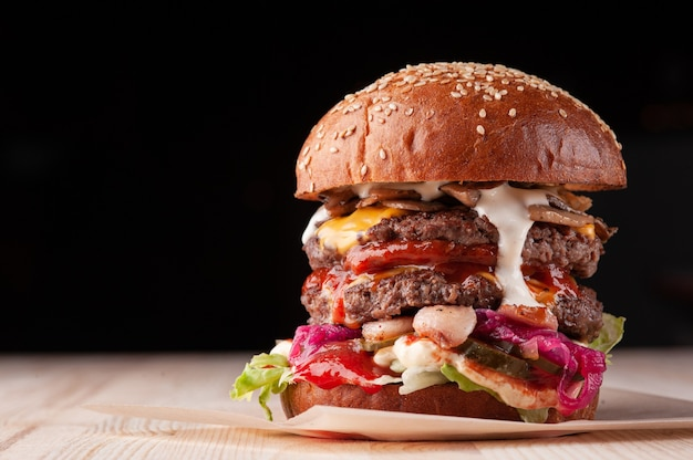 Primo piano di grande doppio hamburger succoso con salsa bianca, formaggio, ketchup, sottaceti, funghi e cipolla rossa su sfondo nero con spazio di copia. messa a fuoco selettiva.