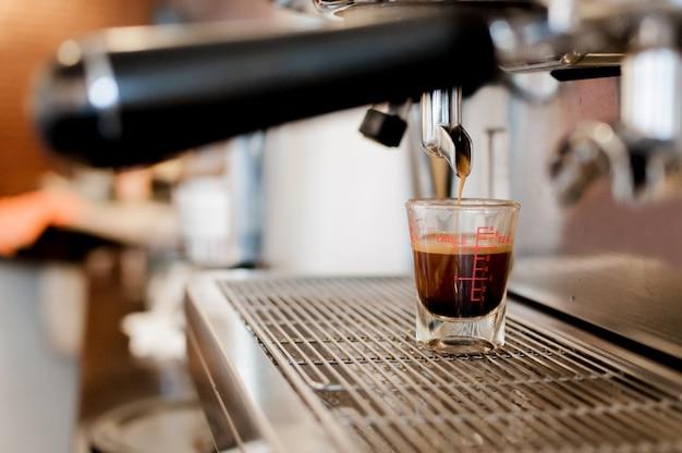 Il caffè nero del primo piano nella tazza di misurazione ha messo sulla caffettiera, macchina per il caffè che fa l'espresso