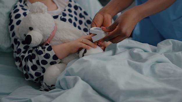 Primo piano dell'infermiera nera che mette l'ossimetro medico sul dito del bambino malato analizzando il battito cardiaco durante...