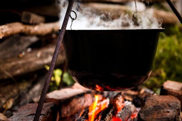 Primo piano di una pentola nera di zuppa calda fumante all'aperto, escursioni e falò che cucinano con brillante