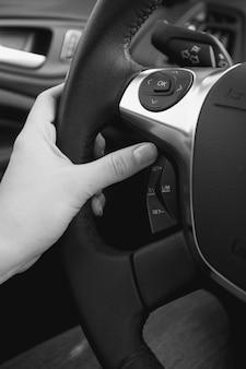 Primo piano foto in bianco e nero dell'autista donna che regola il sistema di controllo della velocità di crociera sul volante