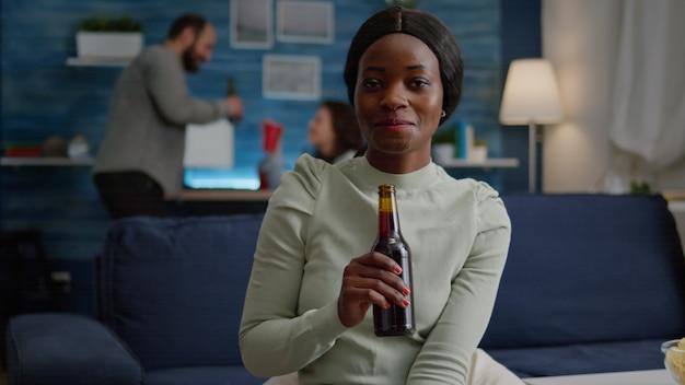 Primo piano del ritratto di donna nera che guarda nella telecamera bevendo birra per il compleanno di un amico friend