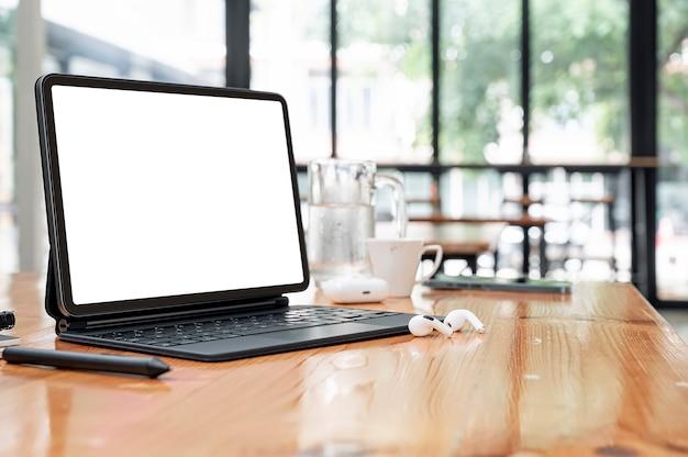 Compressa dello schermo in bianco del primo piano con la tastiera magica sulla tavola di legno nella stanza del caffè.