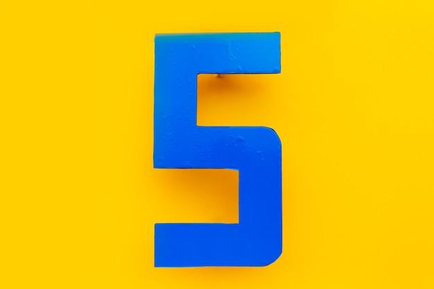 Primo piano del numero esterno blu di 5 su sfondo di colore giallo. lettera di s.