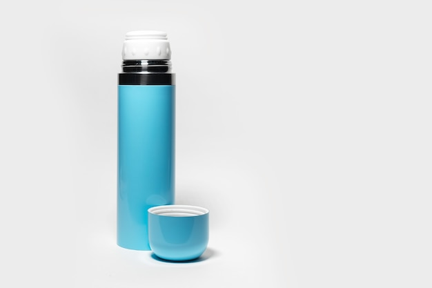 Primo piano di thermos in acciaio blu e tazza di latta isolato su sfondo bianco con spazio di copia.