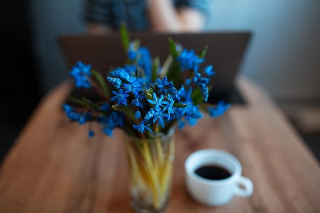 Primo piano delle viole blu sul racconto di legno vicino alla tazza vaga con caffè.