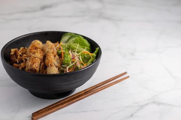 Primo piano di una ciotola di maiale alla griglia vietnamita su tagliatelle e bacchette su un tavolo bianco