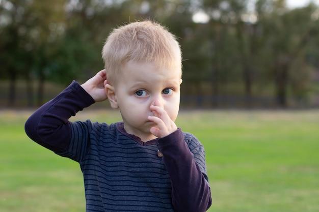 Primo piano il ragazzo è freddo e ha il naso che cola, primo piano muco che scorre dal naso del ragazzino. il bambino ha il naso che cola con il moccio chiaro, virus si ammala all'esterno