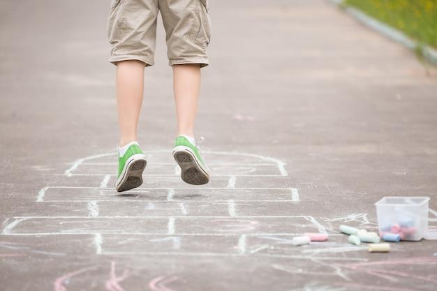 Primo piano delle gambe del ragazzo e della campana disegnata su asfalto