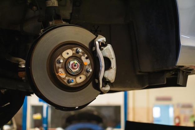 Pastiglie dei freni del primo piano della riparazione del meccanico di automobile manutenzione o controllo del concetto di riparazione dell'auto.