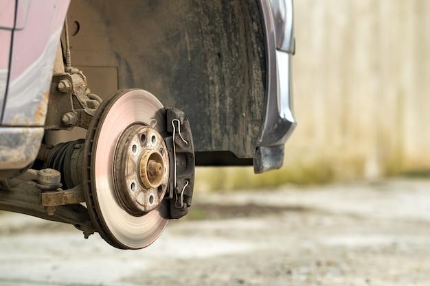 Primo piano del disco di frenatura del veicolo con pinza del freno per la riparazione in fase di sostituzione del nuovo pneumatico. riparazione dei freni dell'auto in garage.