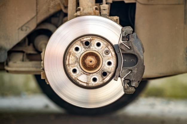 Primo piano del disco di frenatura del veicolo con la pinza del freno per la riparazione in corso di sostituzione di pneumatici nuovi. riparazione freni auto in garage.
