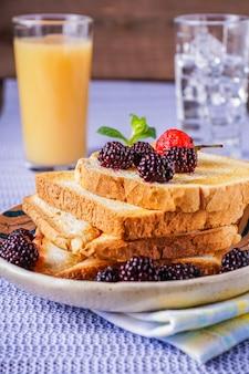 Il primo piano di pane tosta con la bacca fresca, bevanda su fondo, sulla tavola, verticale.