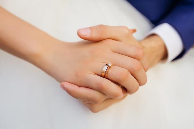 Primo piano della mano della sposa con la fede nuziale. gli sposi si tengono per mano.