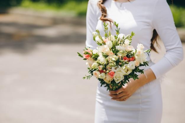 Primo piano della sposa che tiene il bellissimo bouquet da sposa