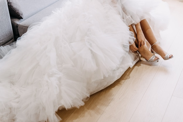 Primo piano della sposa che indossa l'abito da sposa, mettendo sulle sue scarpe.