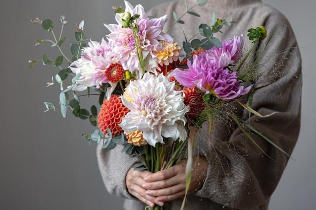 Primo piano di un bouquet festivo luminoso con crisantemi in mani femminili