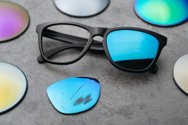 Primo piano di occhiali rotti con lenti colorate danneggiate circondate da lenti diverse
