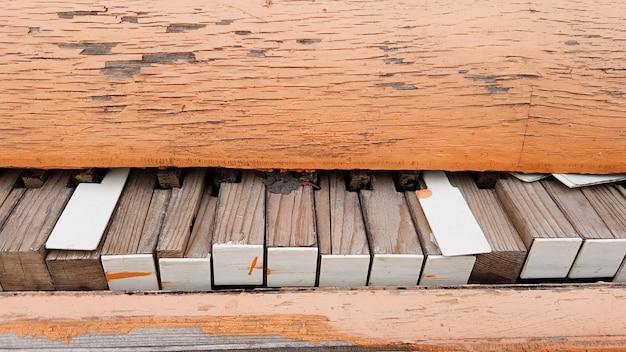 Primo piano di una tastiera di pianoforte rotta di un vecchio pianoforte.