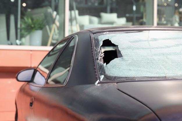 Primo piano del vetro posteriore rotto dell'auto nera