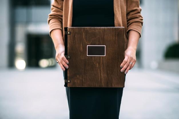 Primo piano di un libro fotografico premio spesso di legno scuro marrone nelle mani di una ragazza. donna in un vestito nero e un maglione beige