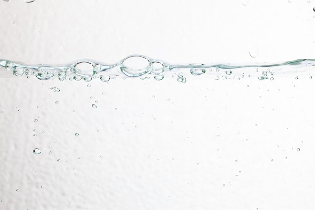 Primo piano bolle sott'acqua su sfondo bianco.