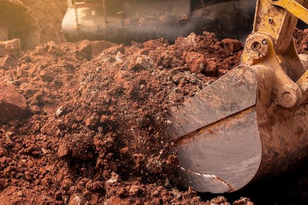 Benna del primo piano dell'escavatore a cucchiaia rovescia che scava il terreno al cantiere. macchina da scavo.