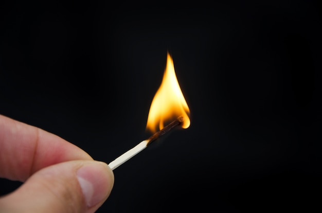 Primo piano del fiammifero acceso in mano sul nero.