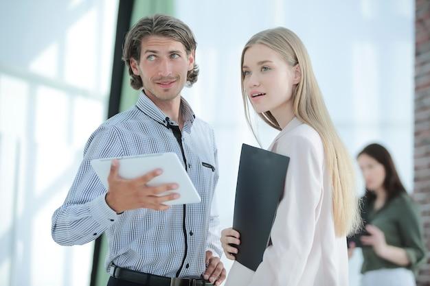 Colleghi di affari del primo piano che stanno sulle persone e sulla tecnologia moderne dell'ufficio