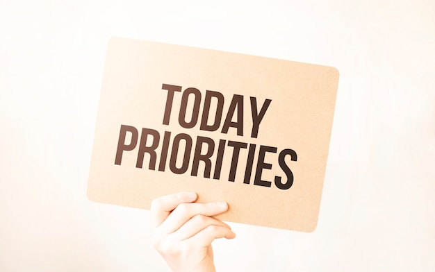 Primo piano business man mano che tiene mostra foglio di carta in bianco. testo oggi priorità