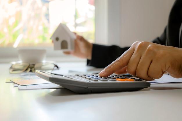 Primo piano delle mani di un uomo d'affari usando una calcolatrice e prendendo appunti
