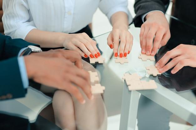 Avvicinamento. squadra di affari che monta i pezzi di puzzle. soluzioni di affari di concetto