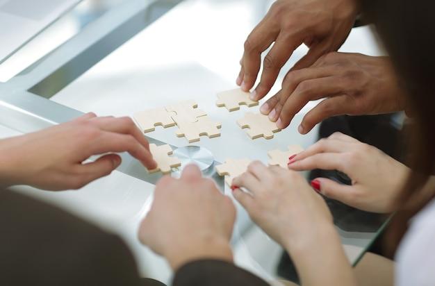 Primo piano del team aziendale assemblaggio di pezzi di un puzzle concetto soluzioni aziendali