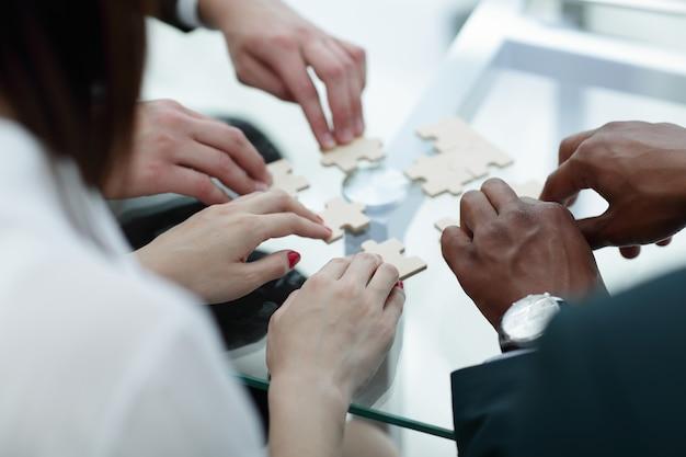 Avvicinamento. team aziendale assemblaggio di pezzi di un puzzle
