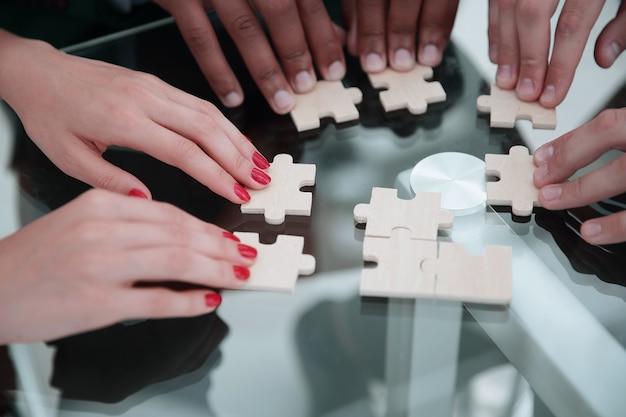 Primo piano.squadra aziendale che assembla puzzle,seduti al tavolo.il concetto di strategia aziendale